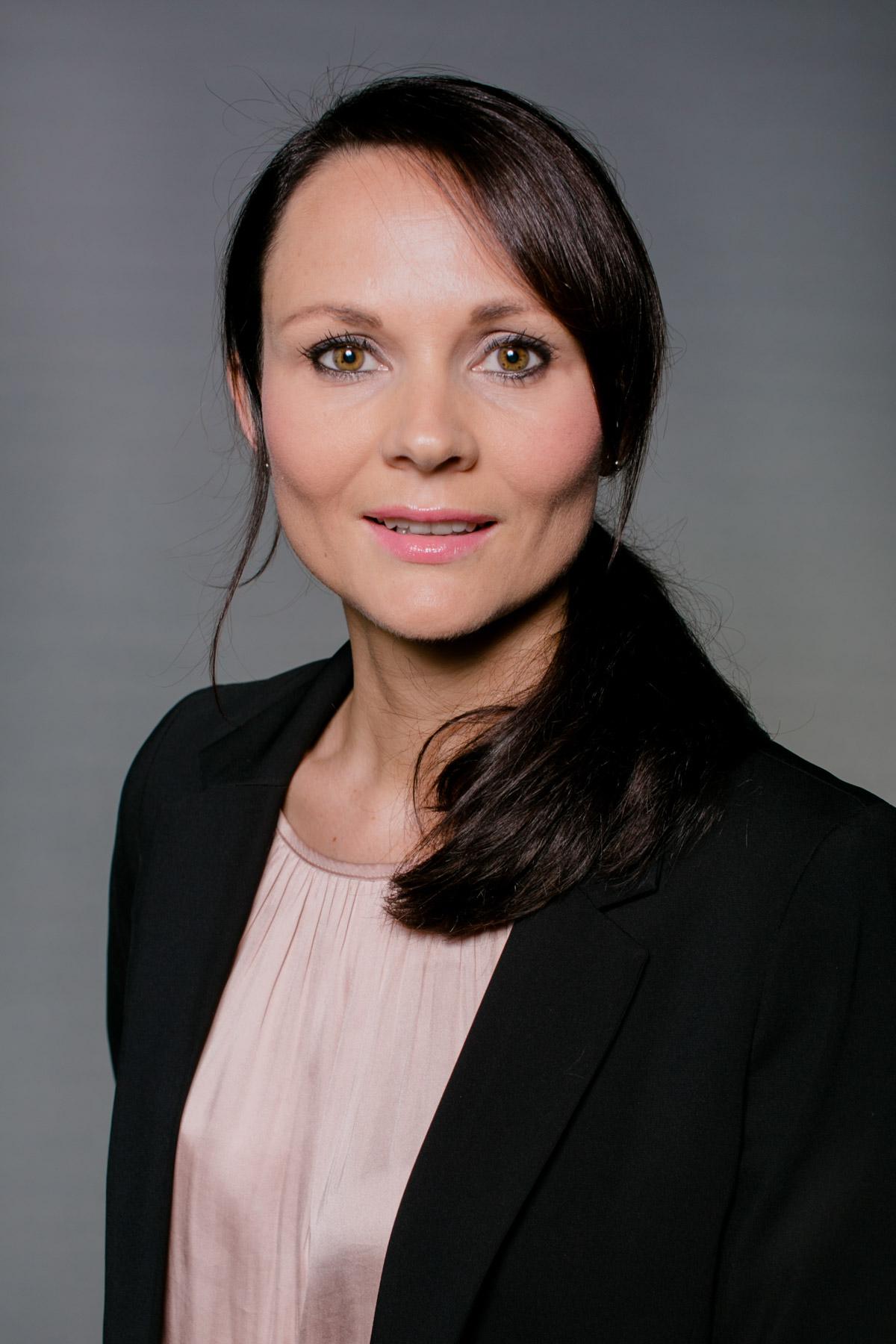 Mitarbeiterfoto einer Mitarbeiterin, klassisch vor grauem Hintergrund